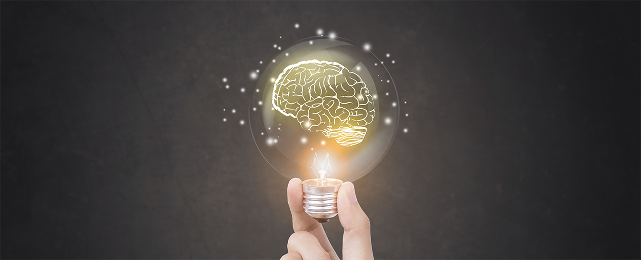 Image of hand held light bulb illuminating with the image of a lit brain inside the bulb