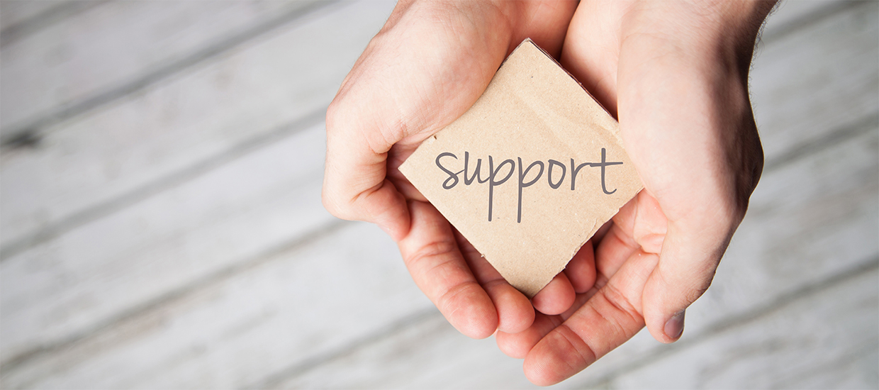 "Image of hands holding a sign that reads ""Support"""