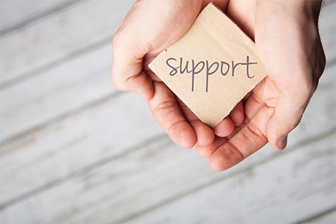 "Image of hands holding a sign reading ""Support"""